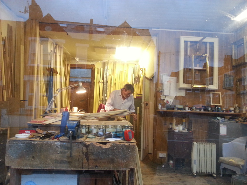 View through the window of a picture framer's workshop with reflections of the street outside